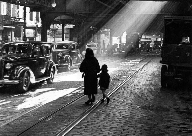 A woman and child walking through New York in the 1920s
