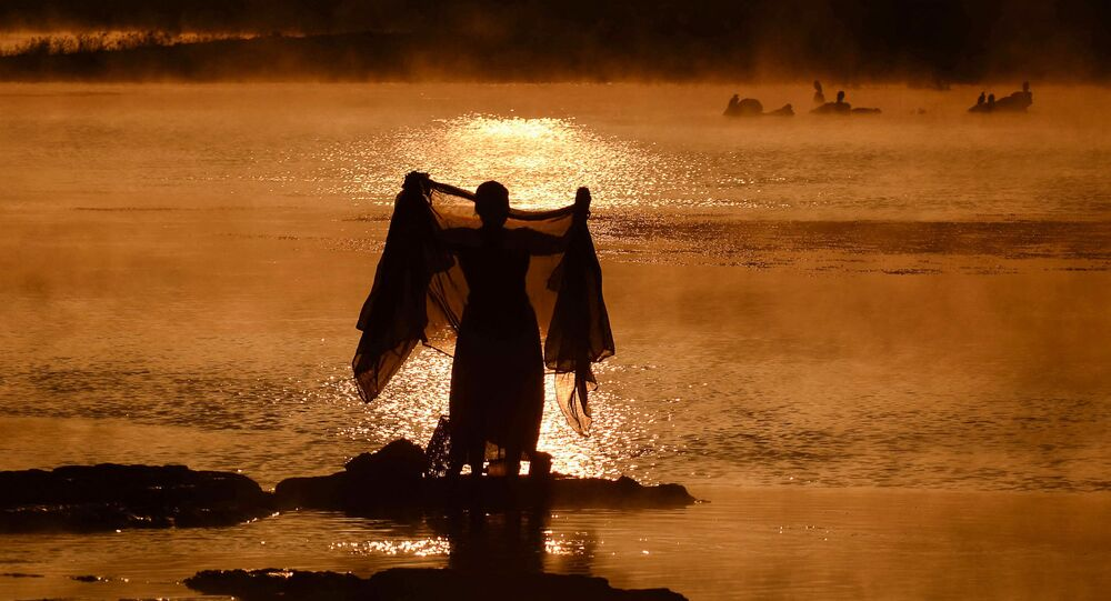 An Indian woman washes a sari in the Narmada River at sunrise on a foggy winter morning in Jabalpur in Madhya Pradesh state on January 2, 2019