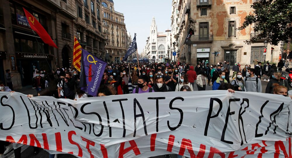 Demonstrators hold a banner during a protest in support of Catalan rapper Pablo Hasel, after he was given a jail sentence on charges of glorifying terrorism and insulting royalty in his songs, in Barcelona, Spain, February 19, 2021