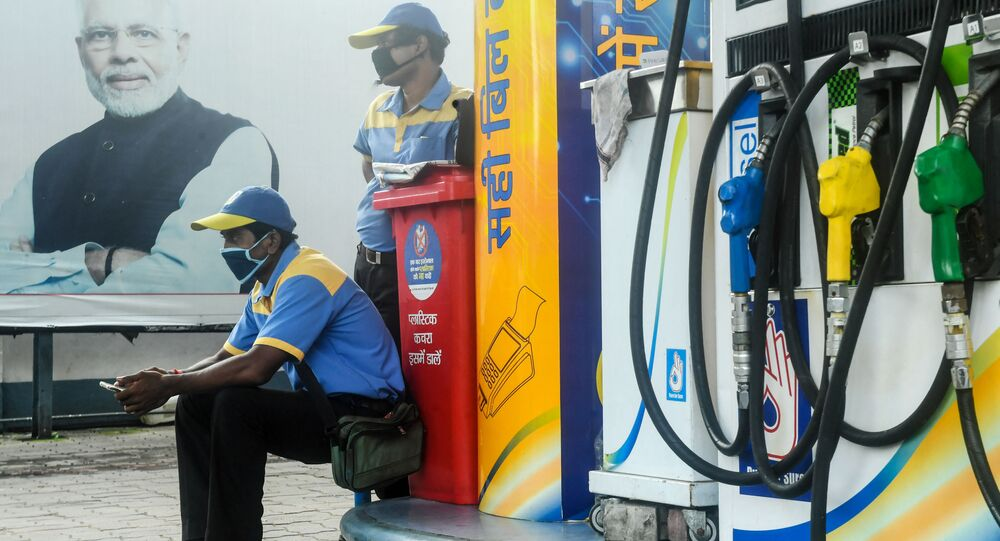 Employees of a petrol station wait for customers near a poster of India's Prime Minister Narendra Modi (L) during a new lockdown imposed by the state government against the surge in COVID-19 coronavirus cases, in Kolkata on 29 July 2020.