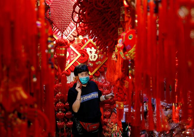 A vendor wearing a face mask following the coronavirus disease (COVID-19) outbreak uses her mobile phone at a market selling Spring Festival ornaments ahead of the Chinese Lunar New Year festivity, in Beijing, China January 27, 2021