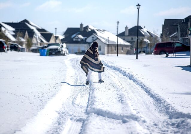 A man walks to his friend's home in a neighbourhood without electricity as snow covers the BlackHawk neighborhood in Pflugerville, Texas, U.S. February 15, 2021. Picture taken February 15, 2021.