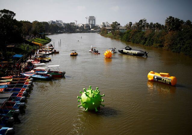 Huge coronavirus-shaped and submarine-shaped balloons float in the Yarkon River during a protest over Israeli governments handling of the coronavirus disease (COVID-19) crisis and Israeli Prime Minister Benjamin Netanyahu's alleged corruption, in Tel Aviv, Israel February 12, 2021.