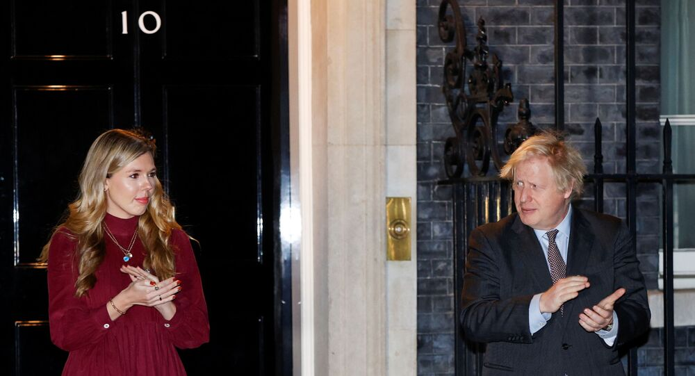 Britain's Prime Minister Boris Johnson and partner Carrie Symonds applaud outside 10 Downing Street during a national clap for late Captain Sir Tom Moore and NHS workers, amidst the coronavirus disease (COVID-19) outbreak, in London, Britain, February 3, 2021.