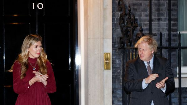 Britain's Prime Minister Boris Johnson and partner Carrie Symonds applaud outside 10 Downing Street during a national clap for late Captain Sir Tom Moore and NHS workers, amidst the coronavirus disease (COVID-19) outbreak, in London, Britain, February 3, 2021.  - Sputnik International
