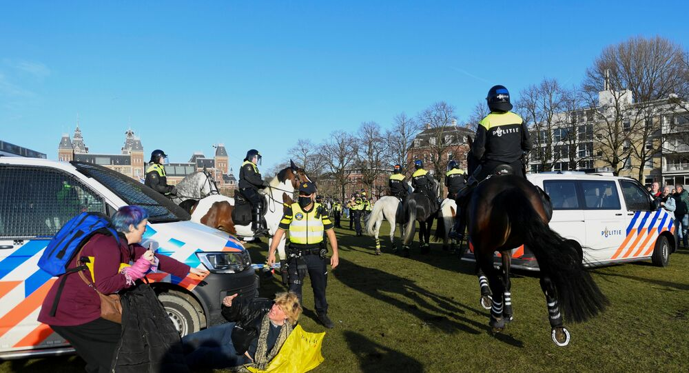 A woman lies on the ground after getting run down by a police officer on a horse, as people protest against the coronavirus disease (COVID-19) restrictions in Amsterdam, Netherlands, February 21, 2021.