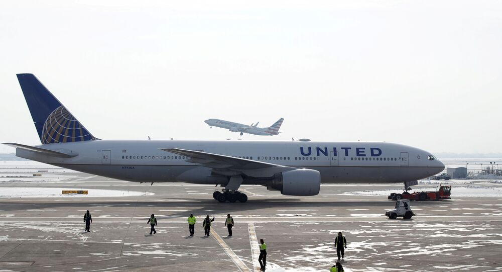 A United Airlines Boeing 777-200ER  plane is towed as an American Airlines Boeing 737 plane departs from O'Hare International Airport in Chicago, Illinois, U.S. Nov. 30, 2018.