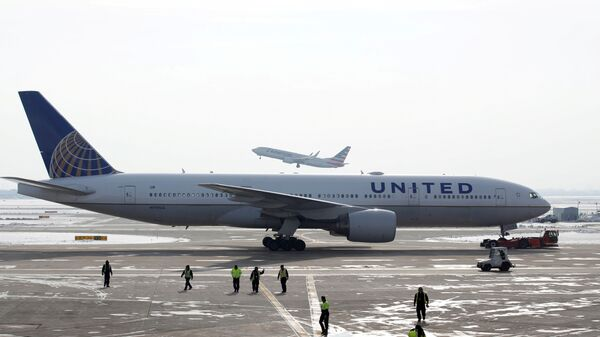 A United Airlines Boeing 777-200ER  plane is towed as an American Airlines Boeing 737 plane departs from O'Hare International Airport in Chicago, Illinois, U.S. Nov. 30, 2018.  - Sputnik International