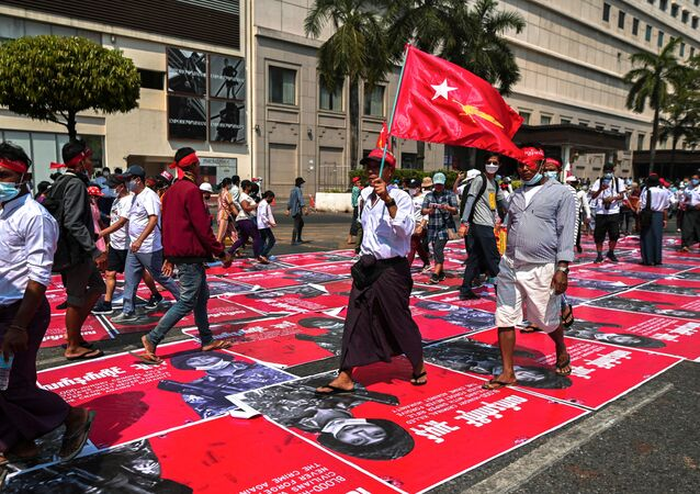 People step on placards showing the photo of an alleged Myanmar Army sniper during a protest against the military coup in Yangon, Myanmar, February 22, 2021.