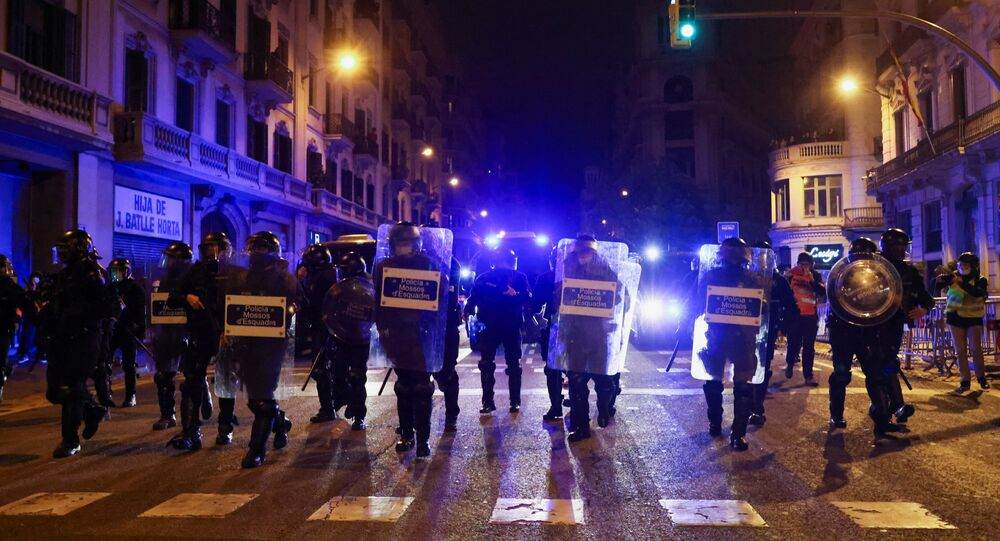 Police officers walk during a protest in support of rap singer Pablo Hasel after he was given a jail sentence on charges of glorifying terrorism and insulting royalty in his songs, in Barcelona, Spain, February 21, 2021.