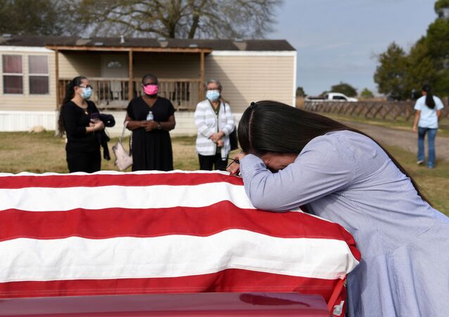 Lila Blanks holds the casket of her husband, Gregory Blanks, 50, who died of the coronavirus disease (COVID-19), ahead of his funeral in San Felipe, Texas, U.S., January 26, 2021