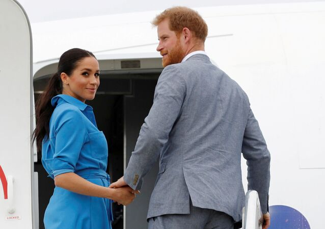 Britain's Prince Harry and Meghan, Duchess of Sussex look on before departing from Fua'amotu International Airport in Tonga October 26, 2018