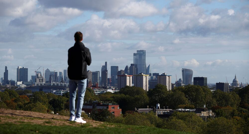 FILE PHOTO: A person looks at the skyline of central London in the background, amid the outbreak of the coronavirus disease (COVID-19), in London, Britain October 15, 2020. REUTERS/Hannah McKay/File Photo