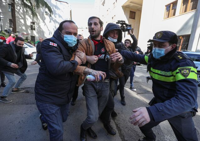 Georgian law enforcement officers detain a man during a demonstration held by opposition supporters near the parliament building in Tbilisi, Georgia 22 February 2021.