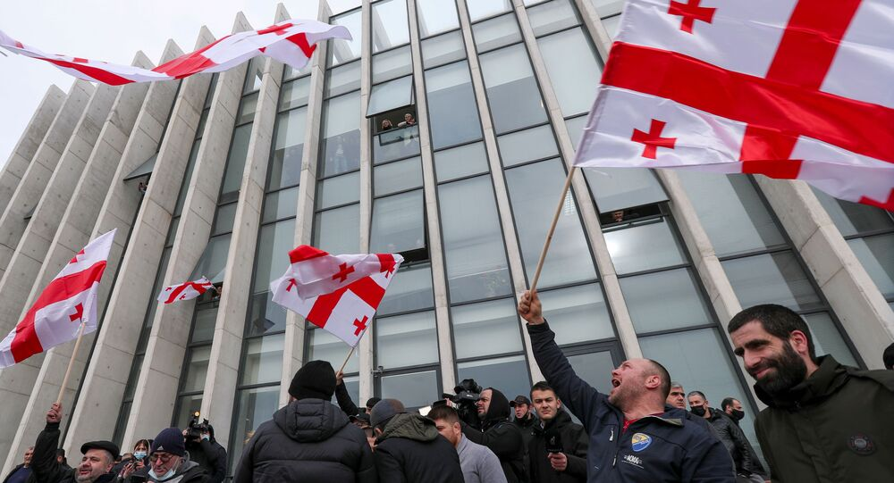 Opposition supporters wave flags following the announcement of Georgian Prime Minister Giorgi Gakharia's resignation outside the headquarters of the United National Movement (UNM) party in Tbilisi, Georgia February 18, 2021.