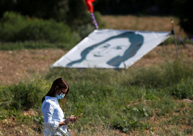 FILE PHOTO: A woman walks past a banner depicting anti-corruption journalist Daphne Caruana Galizia during a commemoration at the site where the journalist was assassinated with a car bomb in 2017, in Bidnija, Malta, October 16, 2020.
