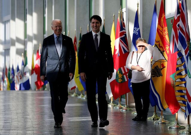 A woman watches as current U.S. President Joe Biden (L) and Canada's Prime Minister Justin Trudeau arrive at the First Ministers' meeting in Ottawa, Ontario, Canada, December 9, 2016