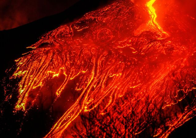 Large streams of red hot lava flow as Mount Etna, Europe's most active volcano, continues to erupt, as seen from the village of Fornazzo, Italy 23 February 2021.