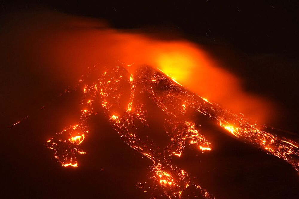 Streams of red hot lava flow as Mount Etna, Europe's most active volcano, erupts, seen from Giarre, Italy, 16 February 2021.
