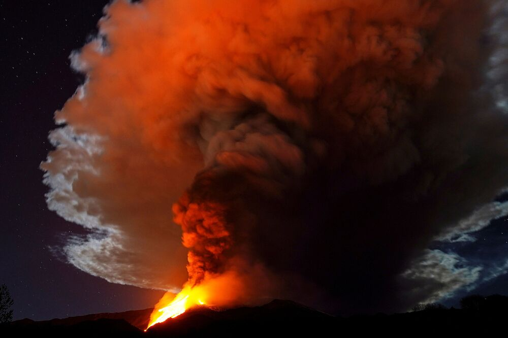 Large streams of red hot lava shoot into the night sky as Mount Etna, Europe's most active volcano, continues to erupt, as seen from the village of Fornazzo, Italy 23 February 2021.