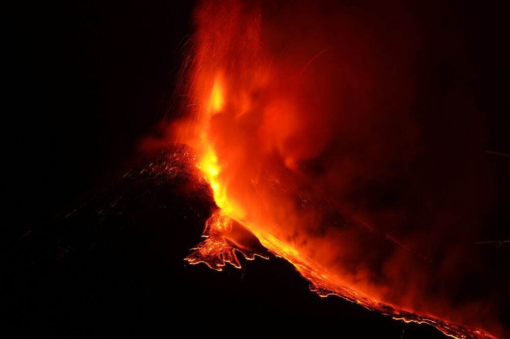 Streams of red hot lava flow as Mount Etna, Europe's most active volcano, continues to erupt, seen from Zafferana Etnea, Italy, 21 February 2021.