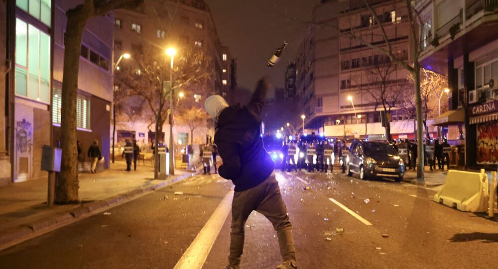 A demonstrator throws a bottle towards police during a protest in support of rap singer Pablo Hasel, after he was given a jail sentence on charges of glorifying terrorism and insulting royalty in his songs, in Barcelona, Spain, February 23, 2021