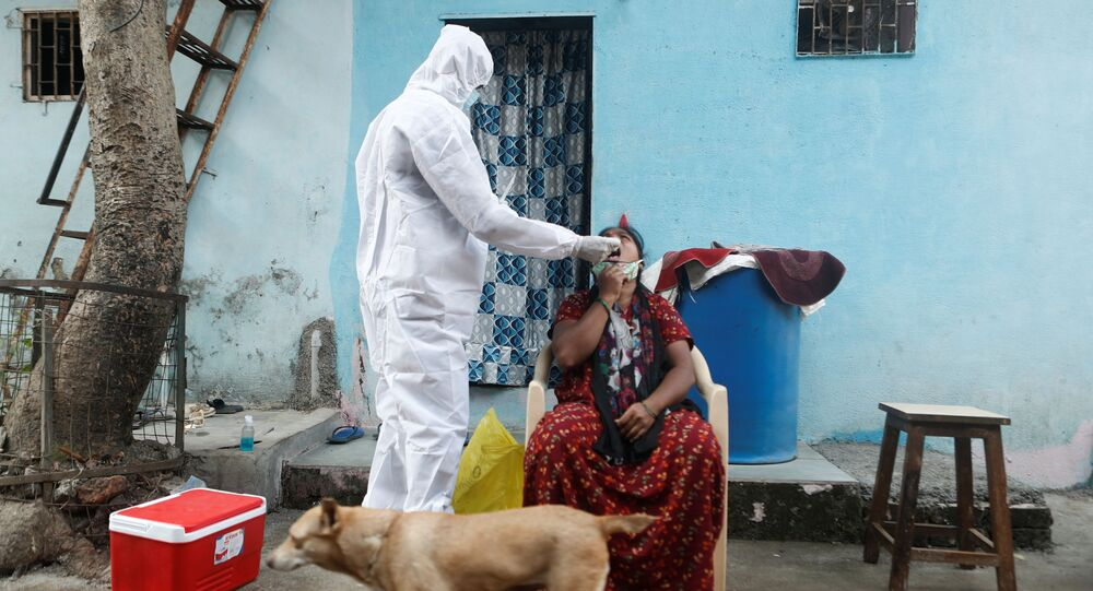 A healthcare worker in personal protective equipment (PPE) collects a swab sample from a resident during a testing campaign for the coronavirus disease (COVID-19), in Mumbai, India, February 23, 2021