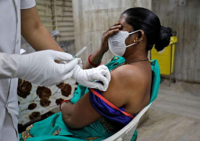 A healthcare worker reacts as she receives the second dose of COVISHIELD, a COVID-19 vaccine manufactured by Serum Institute of India, at a hospital in Ahmedabad, India, February 15, 2021