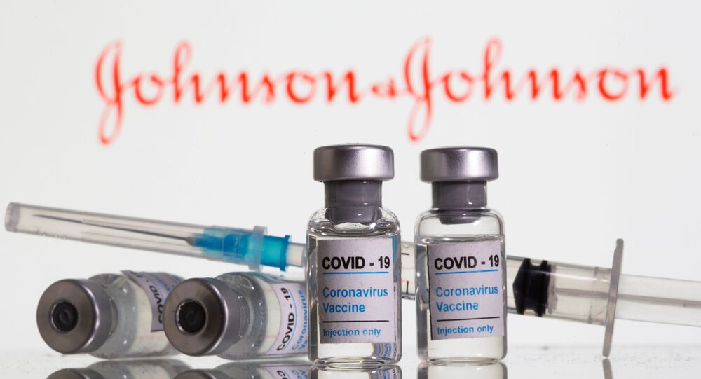 Vials labelled COVID-19 Coronavirus Vaccine and sryinge are seen in front of displayed Johnson&Johnson logo in this illustration taken, February 9, 2021