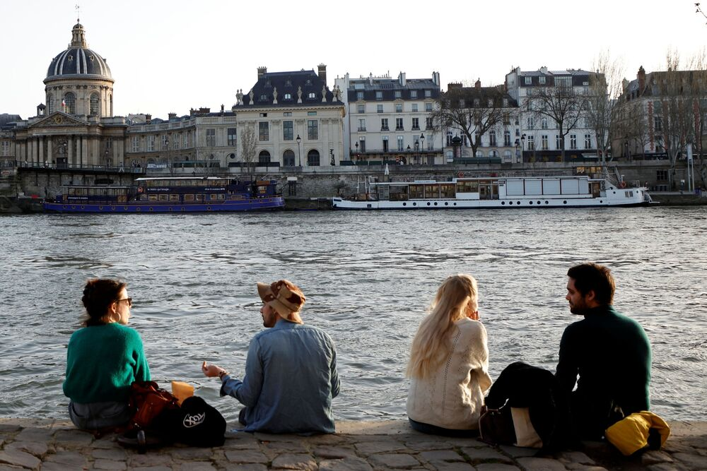 People enjoy sunny, warm weather sitting on the banks of the Seine in Paris amid the coronavirus disease (COVID-19) outbreak in France, 24 February 2021.