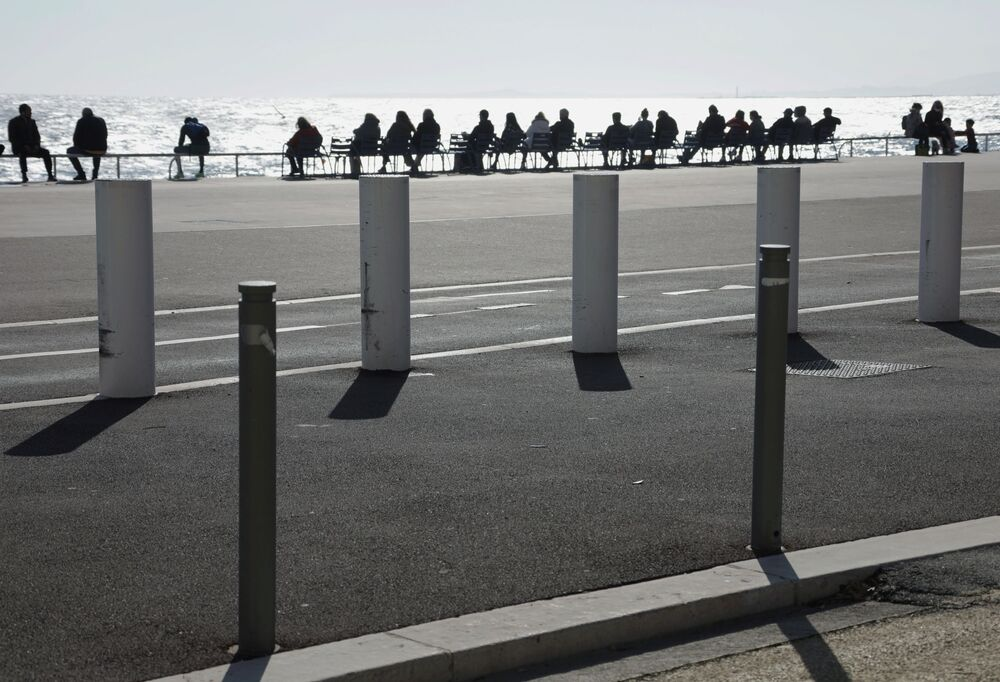 People enjoy the warmth and sunny weather of the Promenade des Anglais in Nice amid the coronavirus disease (COVID-19) outbreak in France, 21 February 2021.