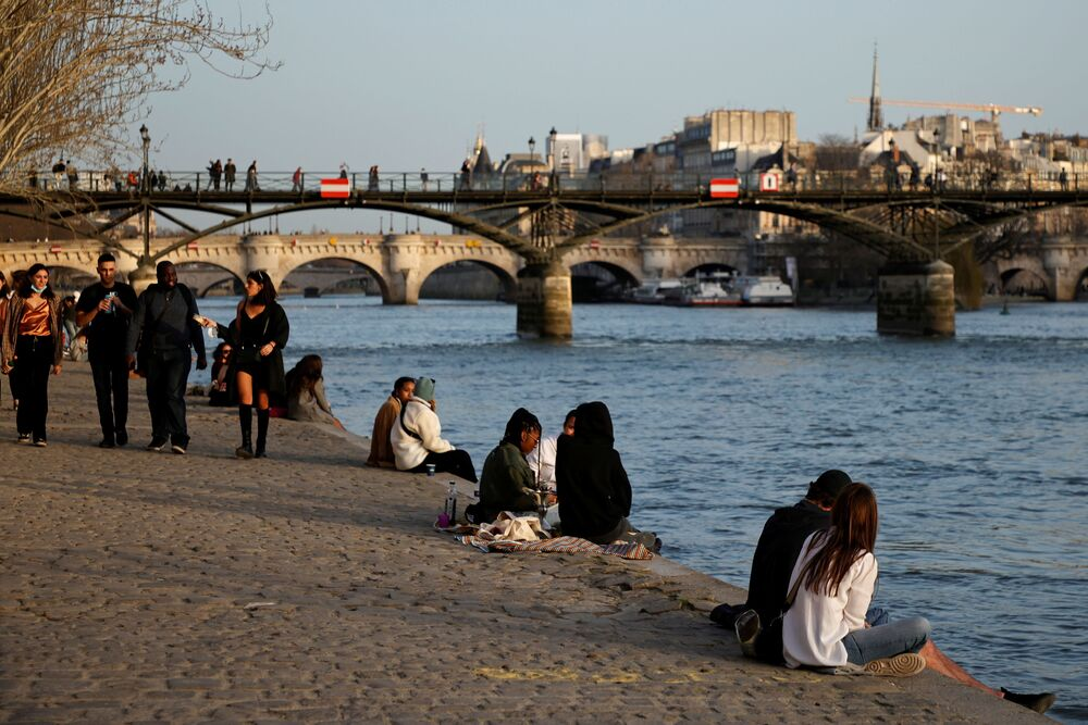 People enjoy a sunny and warm weather sitting on the banks of the Seine in Paris amid the coronavirus disease (COVID-19) outbreak in France, 24 February 2021.