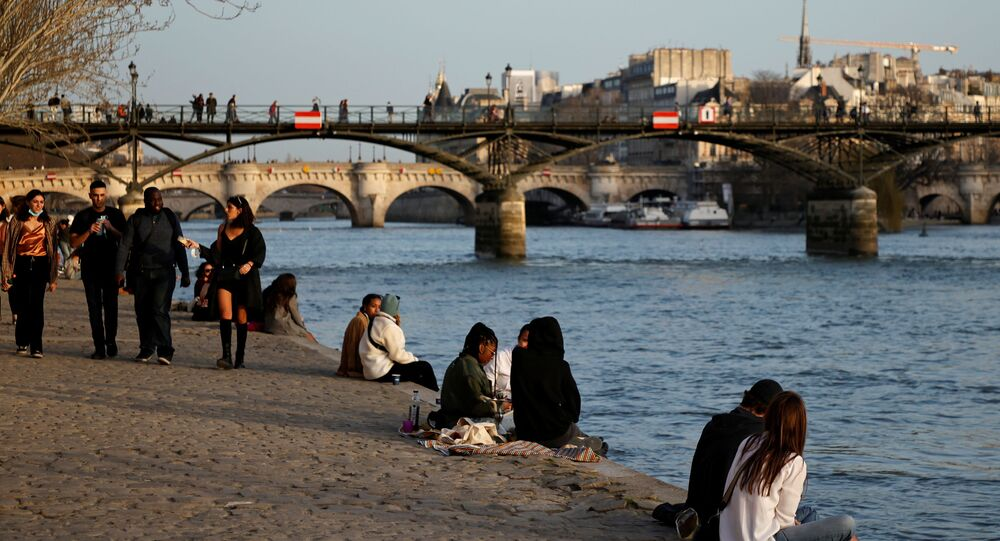 People enjoy a sunny and warm weather sitting on the banks of the River Seine in Paris amid the coronavirus disease (COVID-19) outbreak in France on 24 February 2021.