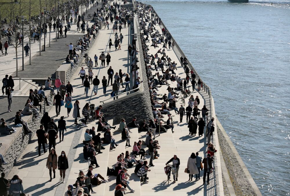 People spend time in the sunshine on the banks of the Rhine amid the coronavirus disease (COVID-19) pandemic in Cologne, Germany, 21 February 2021.