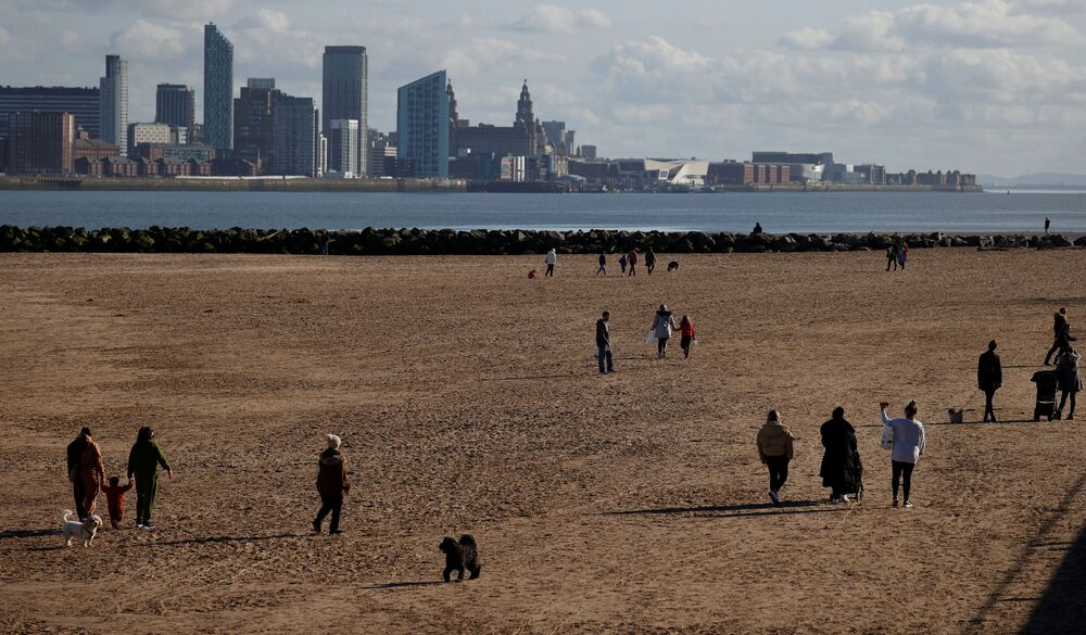 People walk along the beach at New Brighton, England, 22 February 2021.