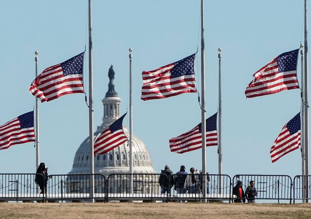 People walk past flags flying at half staff at the Washington Monument in memory of 500,000 deaths due to the coronavirus disease (COVID-19) in Washington, U.S., February 24, 2021.