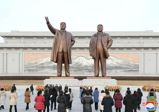 People lay floral tributes in front of the bronze statues of the late leaders Kim Il Sung and his son Kim Jong Il to commemorate the Day of the Shining Star, the birth anniversary of Kim Jong Il, at the Mansudae Grand Monument in Pyongyang, North Korea in this undated photo released by North Korea's Korean Central News Agency (KCNA) on February 17, 2021.