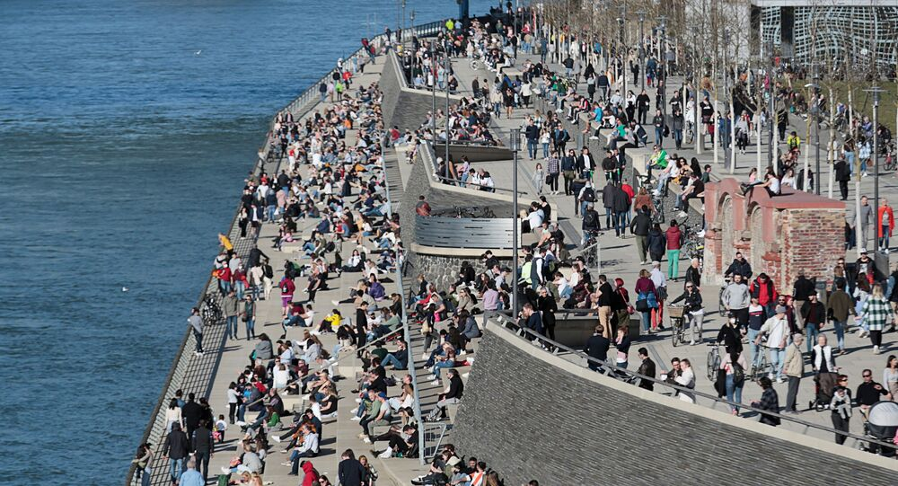 People spend time in the sunshine on the banks of the river Rhine amid the coronavirus disease (COVID-19) pandemic in Cologne, Germany, 21 February 2021.