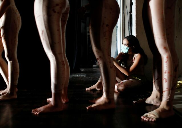 A dancer wearing a protective mask to curb the spread of the coronavirus disease (COVID-19), sits during a virtual dance performance titled 'The Story of Man: In Search of A New Ideal' by Namarina Youth Dance, at the Jakarta Art Building, Indonesia, February 21, 2021. Picture taken February 21, 2021