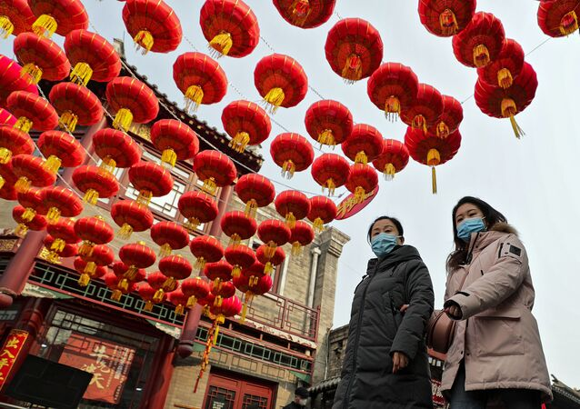 Women wearing face masks to help curb the spread of the coronavirus walk under red lanterns hanging along an alley near the Houhai Lake in celebration of the Lunar New Year in Beijing, Thursday, 11 February  2021. China appeared to be on pace for a slower than normal Lunar New Year travel rush this year after authorities discouraged people from traveling over the holiday to help maintain the nation's control over the ongoing COVID-19 pandemic.