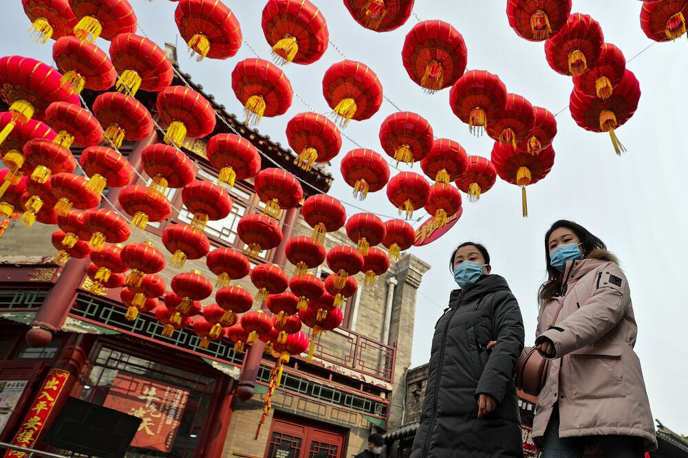 Women wearing face masks to help curb the spread of the coronavirus walk under red lanterns hanging along an alley near the Houhai Lake in celebration of the Lunar New Year in Beijing, 11 February  2021. China appeared to be on pace for a slower than normal Lunar New Year travel rush this year after authorities discouraged people from travelling over the holiday to help maintain the nation's control over the ongoing COVID-19 pandemic.