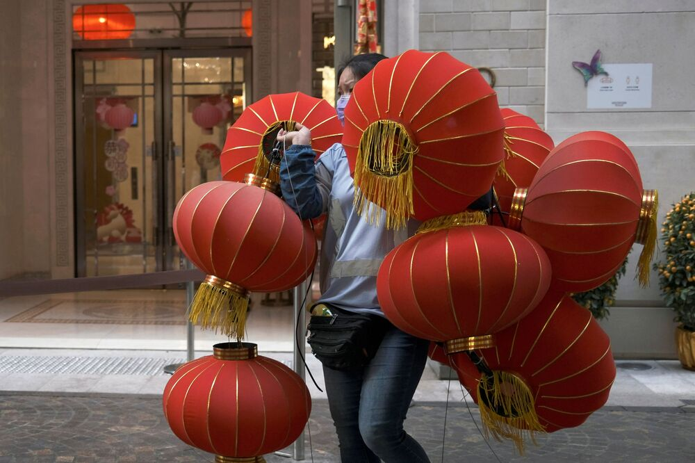 A worker wearing a face mask carries red lanterns, ahead of the Chinese Lunar New Year, following the coronavirus disease (COVID-19) outbreak, in Hong Kong, China 28 January 2021.