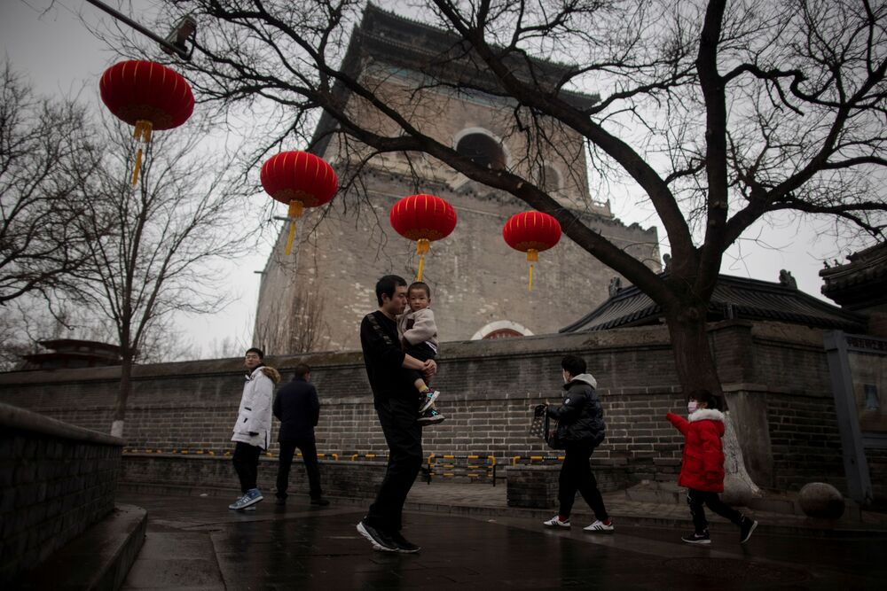 People walk under red lanterns in a historic part of Beijing as China celebrates Lunar New Year of the Ox following an outbreak of the coronavirus disease (COVID-19), China, 14 February 2021.