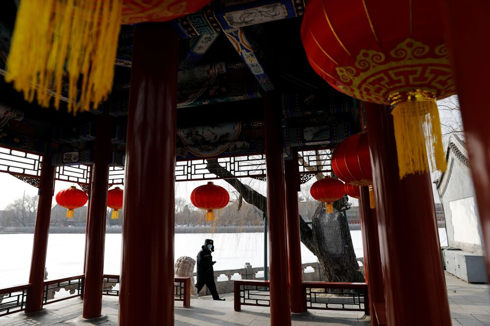 A security guard wearing a face mask walks past a pavilion decorated with red lanterns ahead of the Chinese Lunar New Year festivity, at a park following the coronavirus disease (COVID-19) outbreak in Beijing, China 27 January 2021.