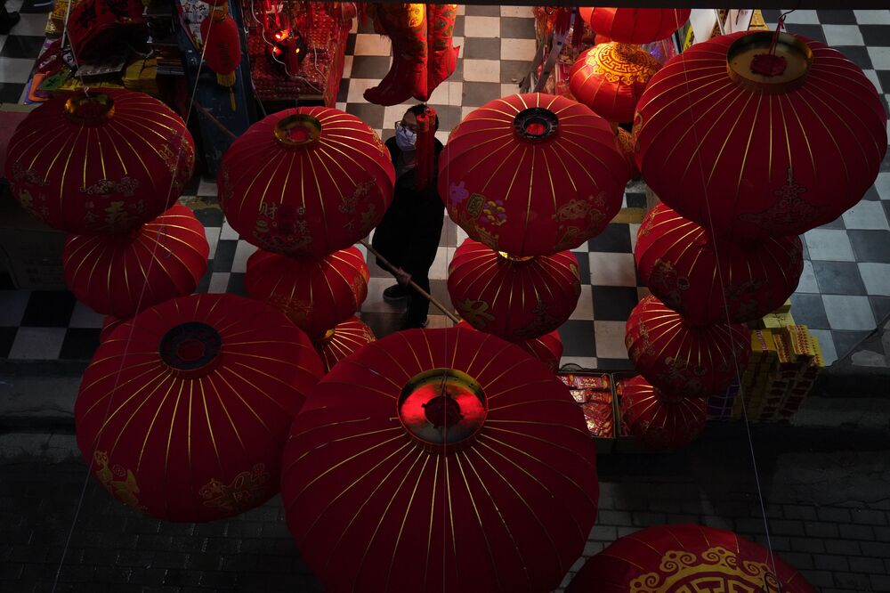 A vendor of Lunar New Year decorations looks up near giant lanterns hung outside a store ahead of the Year of the Ox Chinese Lunar New Year celebrations in Wuhan in central China's Hubei province on 22 January 2021. A recent resurgence in coronavirus cases in China has prompted authorities to curb Lunar New Year activities, impacting a wide swath of industries from airlines, trains, hotels and restaurants to small shops selling decorations for the Year of the Ox.