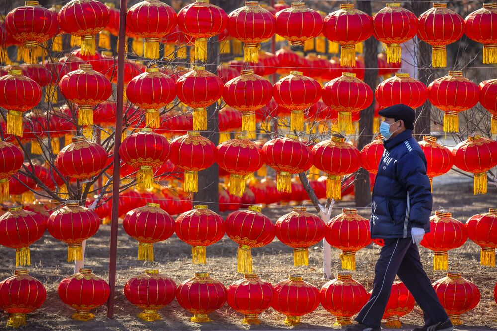 A man wearing a face mask to protect against the spread of the coronavirus walks past a display of lanterns at a public park in Beijing on 5 January 2021. China has designated parts of Hebei province near Beijing as a coronavirus high danger zone after 14 new cases of COVID-19 were found.