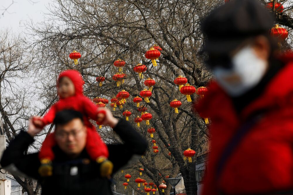 People walk past trees decorated with red lanterns ahead of the Chinese Lunar New Year festivity, following the coronavirus disease (COVID-19) outbreak in Beijing, China 27 January 2021.