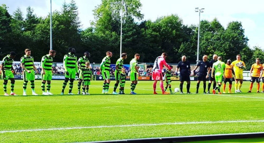 Forest Green Rovers players line up ahead of a match at their stadium in England