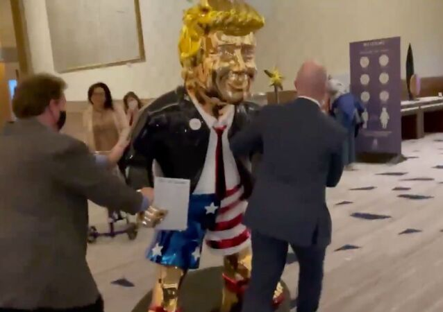 Screenshot captures golden statue of former US President Donald Trump being wheeled toward an event associated with the annual Conservative Police Action Conference.