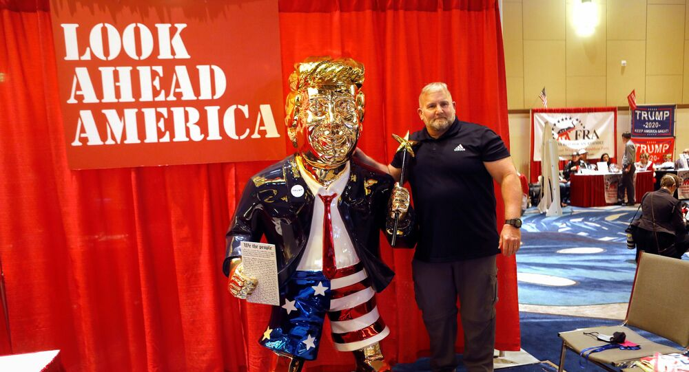 A conference attendee poses next to a statue of former U.S. President Donald Trump at the Conservative Political Action Conference (CPAC) in Orlando, Florida, U.S. February 26, 2021.